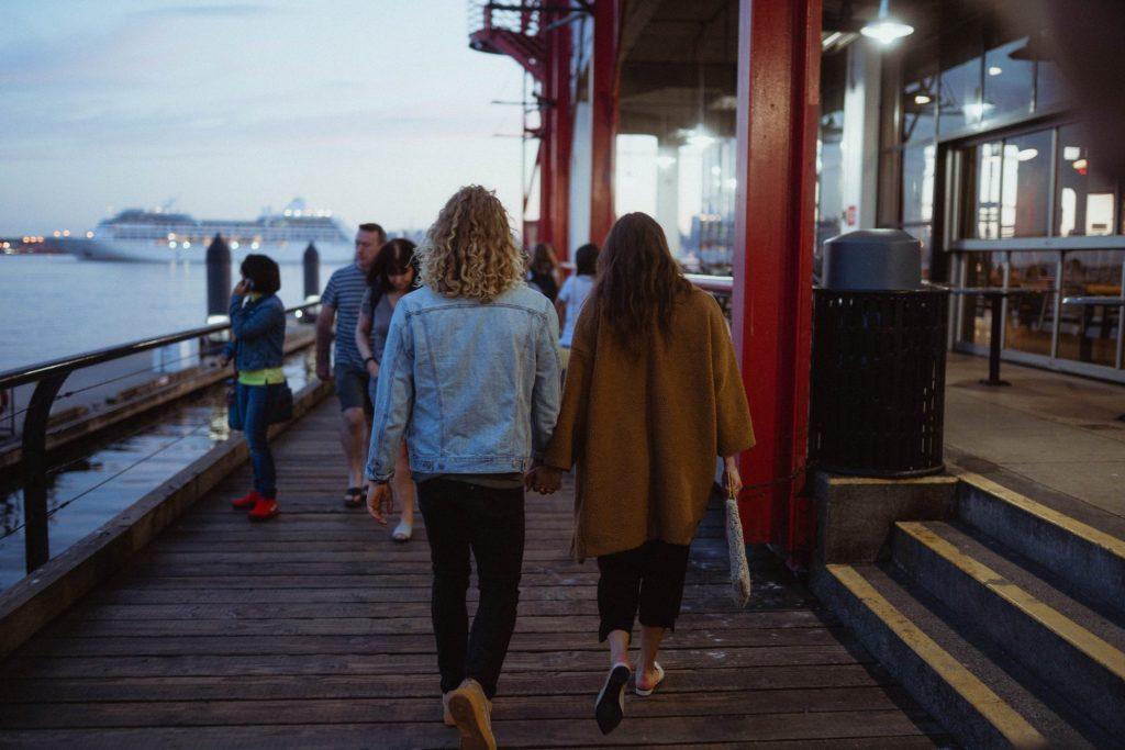 Couple walking along boardwalk at dusk