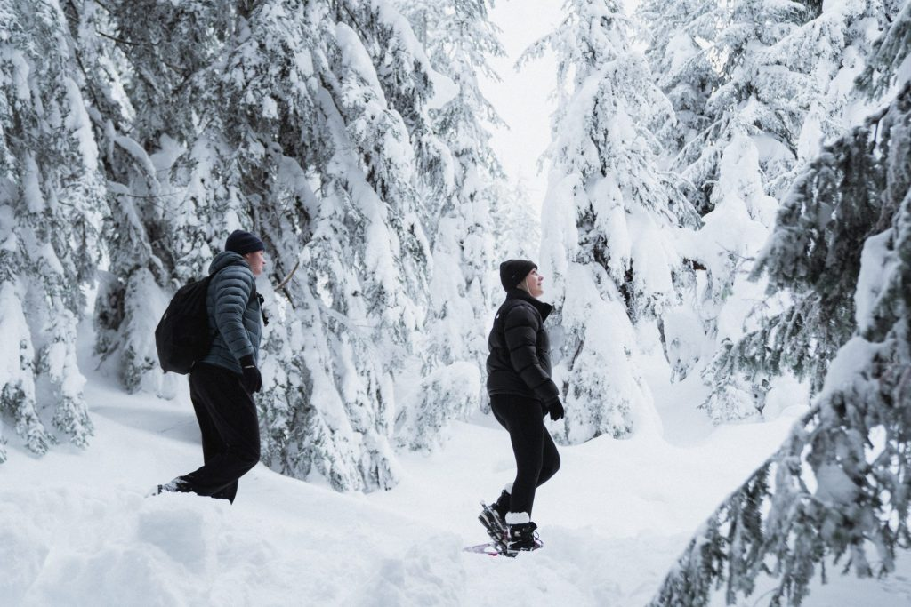 Couple snowshoeing in snowy forest